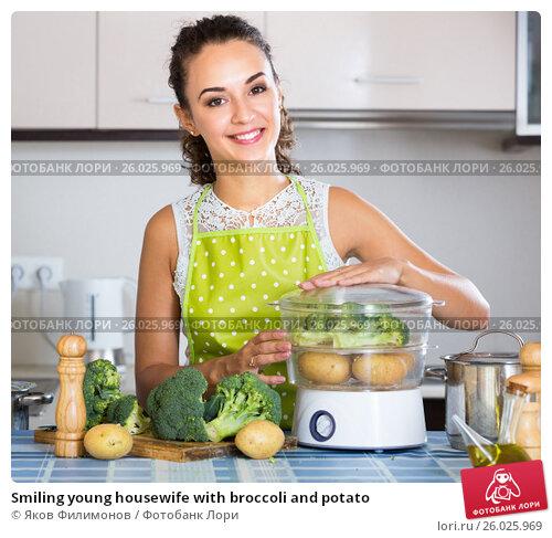 Smiling young housewife with broccoli and potato, фото № 26025969, снято 26 июня 2017 г. (c) Яков Филимонов / Фотобанк Лори