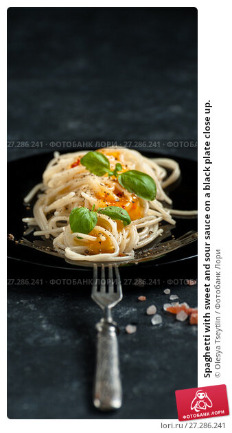 Купить «Spaghetti with sweet and sour sauce on a black plate close up.», фото № 27286241, снято 20 ноября 2017 г. (c) Olesya Tseytlin / Фотобанк Лори