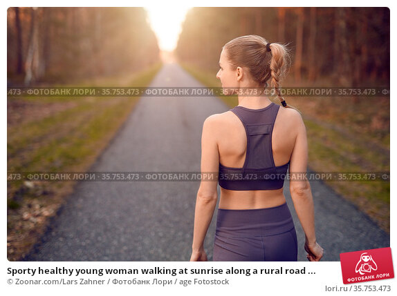 Sporty healthy young woman walking at sunrise along a rural road ... Стоковое фото, фотограф Zoonar.com/Lars Zahner / age Fotostock / Фотобанк Лори