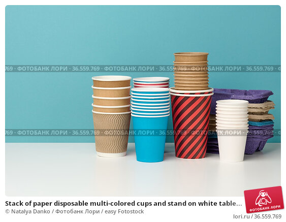 Stack of paper disposable multi-colored cups and stand on white table... Стоковое фото, фотограф Natalya Danko / easy Fotostock / Фотобанк Лори