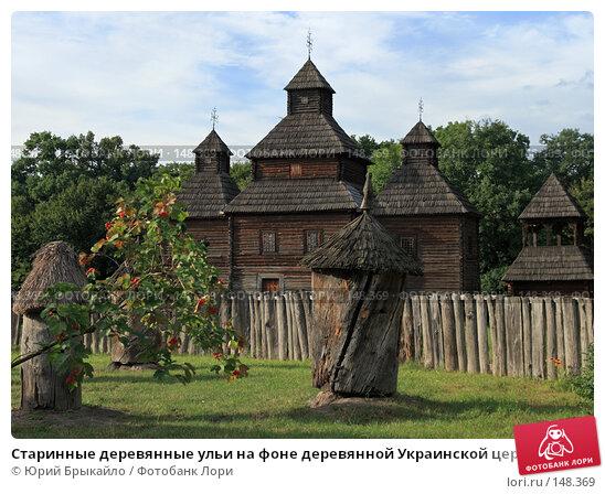 Старинные деревянные ульи на фоне деревянной Украинской церкви, фото № 148369, снято 31 июля 2007 г. (c) Юрий Брыкайло / Фотобанк Лори