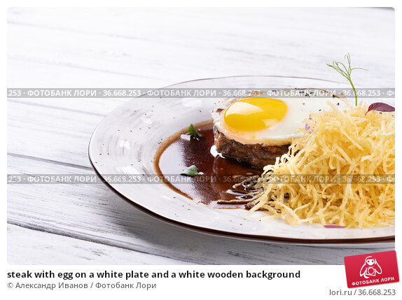steak with egg on a white plate and a white wooden background. Стоковое фото, фотограф Александр Иванов / Фотобанк Лори
