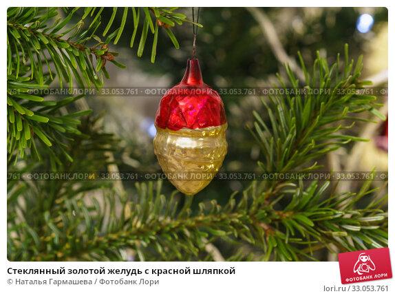 Купить «Стеклянный золотой желудь с красной шляпкой», фото № 33053761, снято 2 января 2020 г. (c) Наталья Гармашева / Фотобанк Лори