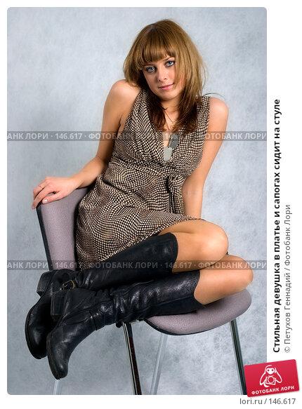 Купить «Стильная девушка в платье и сапогах сидит на стуле», фото № 146617, снято 1 декабря 2007 г. (c) Петухов Геннадий / Фотобанк Лори