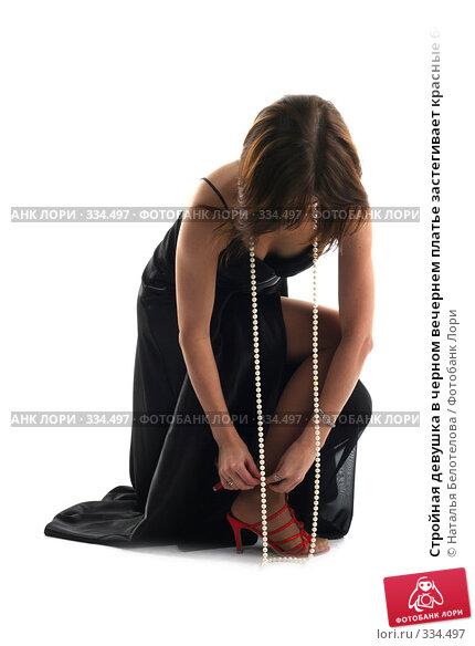 Стройная девушка в черном вечернем платье застегивает красные босоножки, фото № 334497, снято 31 мая 2008 г. (c) Наталья Белотелова / Фотобанк Лори