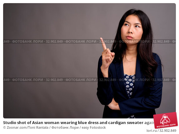 Studio shot of Asian woman wearing blue dress and cardigan sweater against gray background. Стоковое фото, фотограф Zoonar.com/Toni Rantala / easy Fotostock / Фотобанк Лори