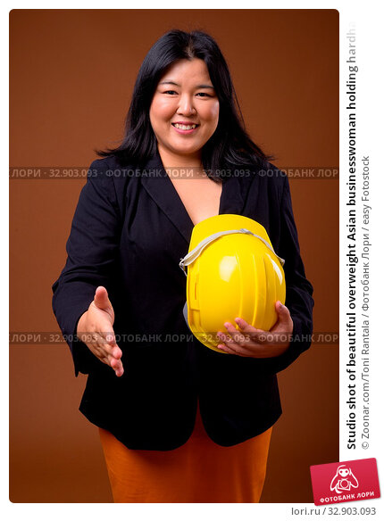 Studio shot of beautiful overweight Asian businesswoman holding hardhat against brown background. Стоковое фото, фотограф Zoonar.com/Toni Rantala / easy Fotostock / Фотобанк Лори