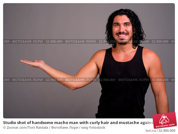 Studio shot of handsome macho man with curly hair and mustache against gray background. Стоковое фото, фотограф Zoonar.com/Toni Rantala / easy Fotostock / Фотобанк Лори