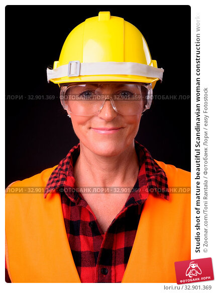 Studio shot of mature beautiful Scandinavian woman construction worker with short hair against black background. Стоковое фото, фотограф Zoonar.com/Toni Rantala / easy Fotostock / Фотобанк Лори