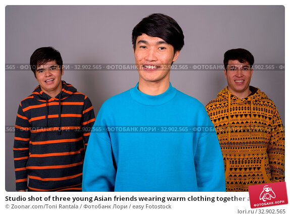 Studio shot of three young Asian friends wearing warm clothing together against gray background. Стоковое фото, фотограф Zoonar.com/Toni Rantala / easy Fotostock / Фотобанк Лори