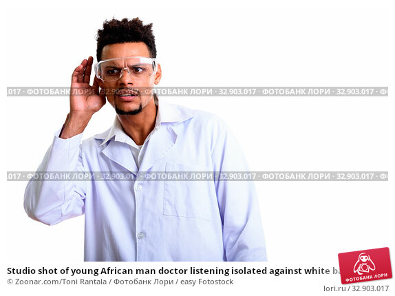 Studio shot of young African man doctor listening isolated against white background. Стоковое фото, фотограф Zoonar.com/Toni Rantala / easy Fotostock / Фотобанк Лори