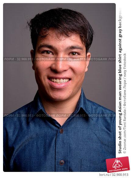 Studio shot of young Asian man wearing blue shirt against gray background. Стоковое фото, фотограф Zoonar.com/Toni Rantala / easy Fotostock / Фотобанк Лори