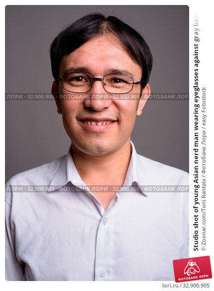 Studio shot of young Asian nerd man wearing eyeglasses against gray background. Стоковое фото, фотограф Zoonar.com/Toni Rantala / easy Fotostock / Фотобанк Лори