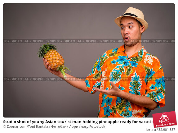 Studio shot of young Asian tourist man holding pineapple ready for vacation against gray background. Стоковое фото, фотограф Zoonar.com/Toni Rantala / easy Fotostock / Фотобанк Лори