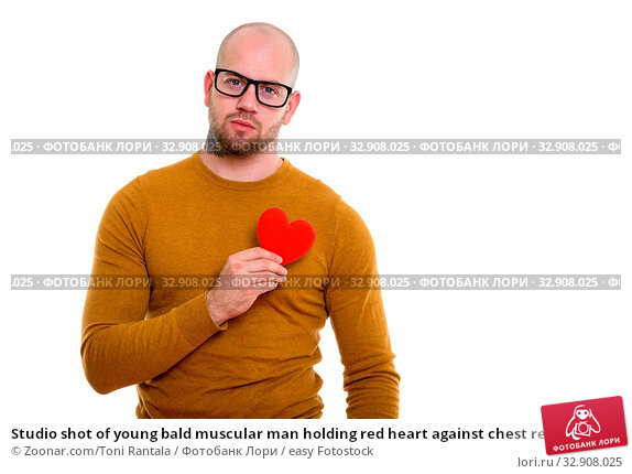 Studio shot of young bald muscular man holding red heart against chest ready for Valentine's day. Стоковое фото, фотограф Zoonar.com/Toni Rantala / easy Fotostock / Фотобанк Лори