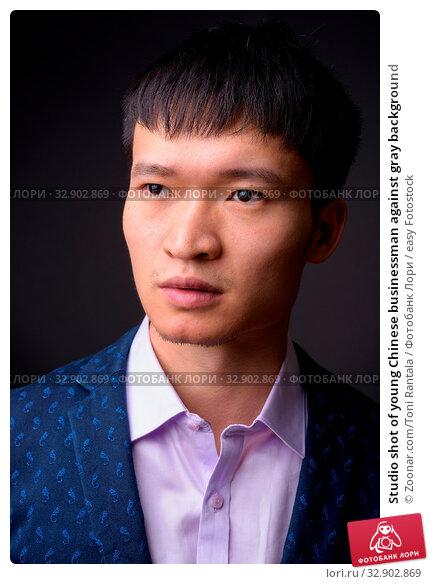 Studio shot of young Chinese businessman against gray background. Стоковое фото, фотограф Zoonar.com/Toni Rantala / easy Fotostock / Фотобанк Лори