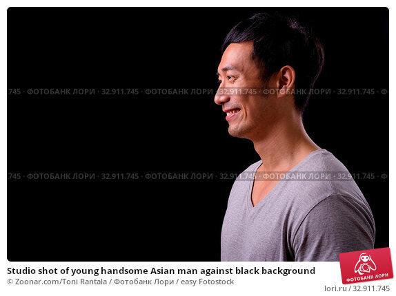 Studio shot of young handsome Asian man against black background. Стоковое фото, фотограф Zoonar.com/Toni Rantala / easy Fotostock / Фотобанк Лори