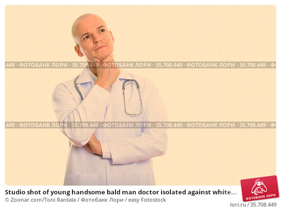 Studio shot of young handsome bald man doctor isolated against white... Стоковое фото, фотограф Zoonar.com/Toni Rantala / easy Fotostock / Фотобанк Лори