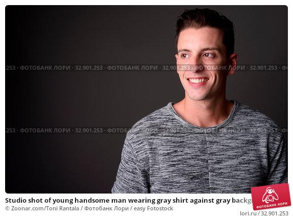Studio shot of young handsome man wearing gray shirt against gray background. Стоковое фото, фотограф Zoonar.com/Toni Rantala / easy Fotostock / Фотобанк Лори