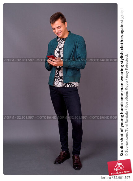 Studio shot of young handsome man wearing stylish clothes against gray background. Стоковое фото, фотограф Zoonar.com/Toni Rantala / easy Fotostock / Фотобанк Лори
