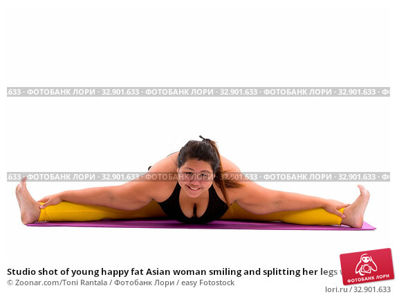 Studio shot of young happy fat Asian woman smiling and splitting her legs while looking at camera. Стоковое фото, фотограф Zoonar.com/Toni Rantala / easy Fotostock / Фотобанк Лори