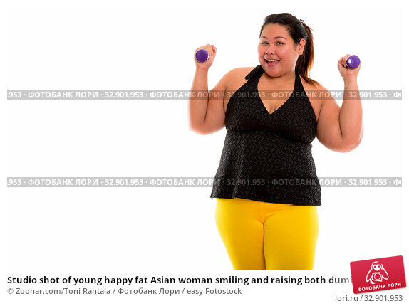 Studio shot of young happy fat Asian woman smiling and raising both dumbbells. Стоковое фото, фотограф Zoonar.com/Toni Rantala / easy Fotostock / Фотобанк Лори