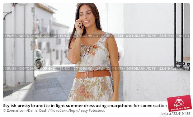 Купить «Stylish pretty brunette in light summer dress using smarpthone for conversation while posing at sunny street and smiling away.», фото № 32419433, снято 5 июля 2020 г. (c) easy Fotostock / Фотобанк Лори