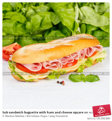 Sub sandwich baguette with ham and cheese square on wooden board wood. Стоковое фото, фотограф Markus Mainka / easy Fotostock / Фотобанк Лори