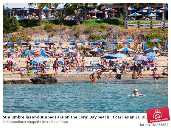 Купить «Sun umbrellas and sunbeds are on the Coral Bay beach. It carries an EU Blue Flag. It is a popular tourist resort in the Peyia municipality on the Mediterranean sea. Cyprus», фото № 32934557, снято 20 сентября 2013 г. (c) Кекяляйнен Андрей / Фотобанк Лори