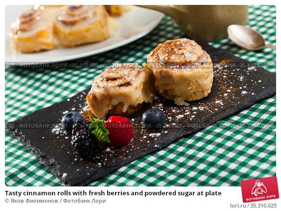 Tasty cinnamon rolls with fresh berries and powdered sugar at plate. Стоковое фото, фотограф Яков Филимонов / Фотобанк Лори