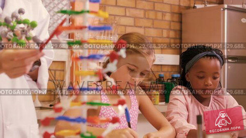 Купить «Teacher assisting student in studying molecule model in laboratory», видеоролик № 29688309, снято 6 марта 2016 г. (c) Wavebreak Media / Фотобанк Лори