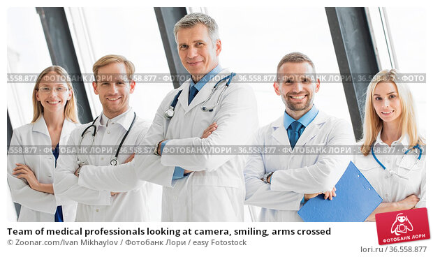 Team of medical professionals looking at camera, smiling, arms crossed. Стоковое фото, фотограф Zoonar.com/Ivan Mikhaylov / easy Fotostock / Фотобанк Лори