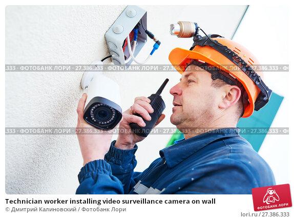 Купить «Technician worker installing video surveillance camera on wall», фото № 27386333, снято 22 декабря 2016 г. (c) Дмитрий Калиновский / Фотобанк Лори