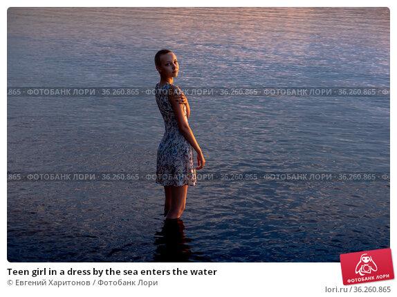 Teen girl in a dress by the sea enters the water. Стоковое фото, фотограф Евгений Харитонов / Фотобанк Лори