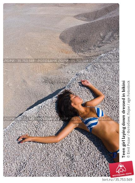Teen girl laying down dressed in bikini. Стоковое фото, фотограф Emil Pozar / age Fotostock / Фотобанк Лори