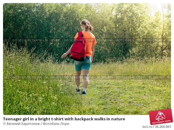 Teenager girl in a bright t-shirt with backpack walks in nature. Стоковое фото, фотограф Евгений Харитонов / Фотобанк Лори