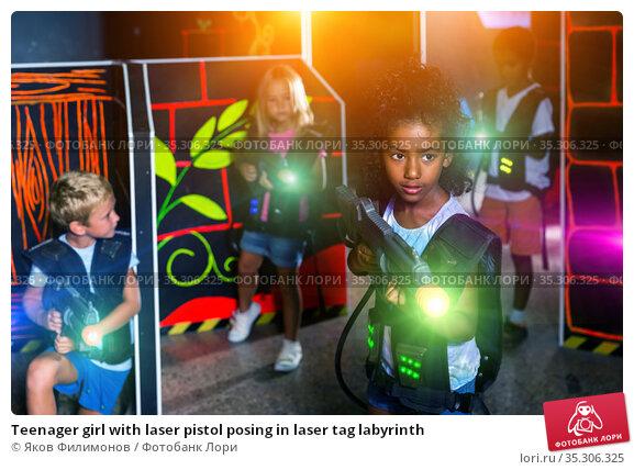Teenager girl with laser pistol posing in laser tag labyrinth. Стоковое фото, фотограф Яков Филимонов / Фотобанк Лори