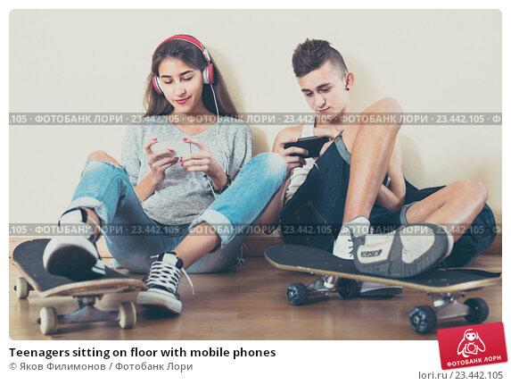 Купить «Teenagers sitting on floor with mobile phones», фото № 23442105, снято 19 июля 2019 г. (c) Яков Филимонов / Фотобанк Лори