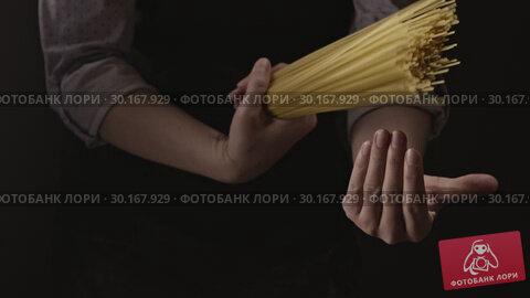 Купить «The bunch of raw italian spaghetti in a woman's hands on a dark background. Slow motion, Full HD video, 240fps, 1080p.», видеоролик № 30167929, снято 31 августа 2018 г. (c) Ярослав Данильченко / Фотобанк Лори