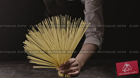 Купить «The bunch of raw spaghetti in female hands on black wood vintage table on a black background. Slow motion, Full HD video, 240fps, 1080p.», видеоролик № 33699645, снято 31 августа 2018 г. (c) Ярослав Данильченко / Фотобанк Лори