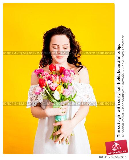 Купить «The cute girl with curly hair holds beautiful tulips», фото № 32542913, снято 9 декабря 2019 г. (c) easy Fotostock / Фотобанк Лори