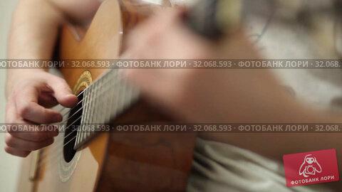 The guitarist plays an acoustic guitar. Guitarist hand and fretboard closeup. Стоковое видео, видеограф Павлов Максим / Фотобанк Лори