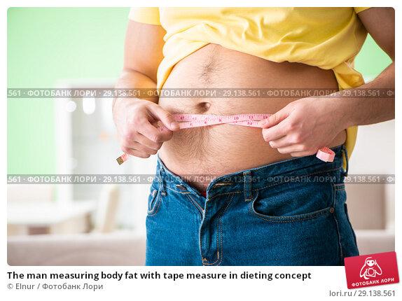 Купить «The man measuring body fat with tape measure in dieting concept», фото № 29138561, снято 11 мая 2018 г. (c) Elnur / Фотобанк Лори