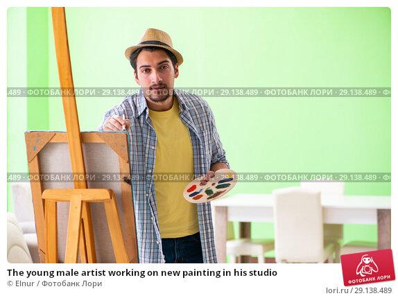 Купить «The young male artist working on new painting in his studio», фото № 29138489, снято 10 мая 2018 г. (c) Elnur / Фотобанк Лори