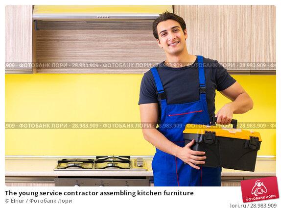 Купить «The young service contractor assembling kitchen furniture», фото № 28983909, снято 19 июня 2018 г. (c) Elnur / Фотобанк Лори