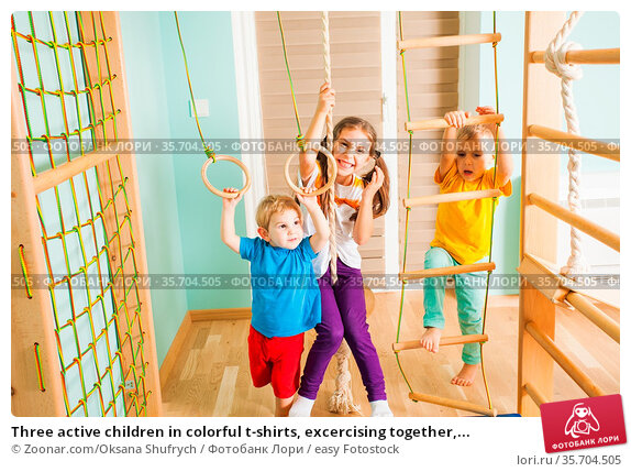 Three active children in colorful t-shirts, excercising together,... Стоковое фото, фотограф Zoonar.com/Oksana Shufrych / easy Fotostock / Фотобанк Лори