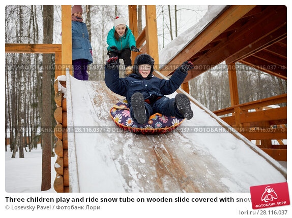 Купить «Three children play and ride snow tube on wooden slide covered with snow on winter day», фото № 28116037, снято 4 февраля 2017 г. (c) Losevsky Pavel / Фотобанк Лори