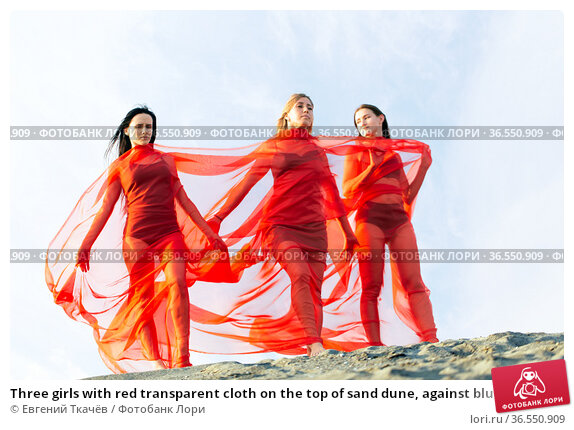 Three girls with red transparent cloth on the top of sand dune, against blue sky. Стоковое фото, фотограф Евгений Ткачёв / Фотобанк Лори