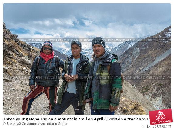Купить «Three young Nepalese on a mountain trail on April 6, 2018 on a track around Annapurna, Nepal», фото № 28728117, снято 6 апреля 2018 г. (c) Валерий Смирнов / Фотобанк Лори