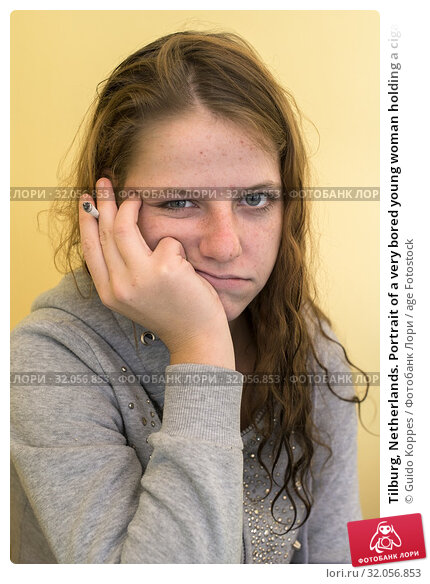 Tilburg, Netherlands. Portrait of a very bored young woman holding a cigarette. Стоковое фото, фотограф Guido Koppes / age Fotostock / Фотобанк Лори